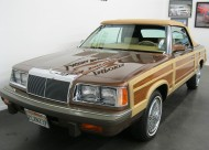 For 1986, LeBaron front and rear fascias were redesigned.  As this picture shows, headlight assemblies, fender corners, and bumpers were rounded for a more aerodynamic look.  The shape of wood trim along the front and rear fenders was revised.