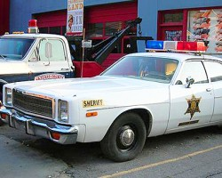 Parked outside the museum are a 1970s Dodge Monaco police car and Ford towtruck also used in the original television show Dukes of Hazzard.  (Photo credit: Hollywood Star Cars Museum)