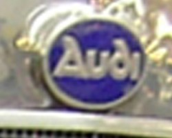 Audi was founded in 1909 by August Horch, after being ousted from Horch MotorWerke he had started a decade previously in 1899. Legally unable to use his own name, his young son studying Latin realized that the latin translation of Horch (which meant HARK or HEAR in German) was the word AUDI. Horch loved the idea, and used it - creating this logo. The original lettering font used here survives today.  (Photo credit: Sean Connor)