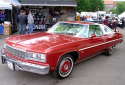 A full view of a 1976 Chevrolet Caprice Classic coupe equipped with color matched wheel covers.