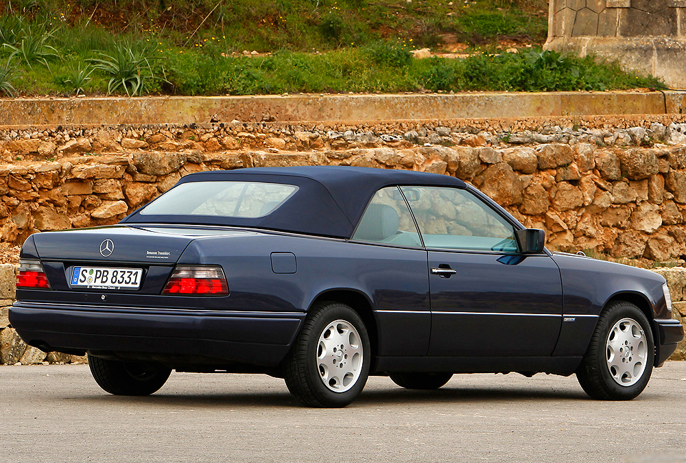 Rear 3/4s view of a Euro E320 Cabriolet with matching color body and plastic cladding.  (Photo credit: Mercedes-Benz Classic)