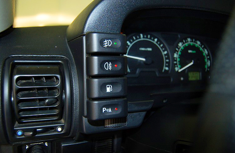 This button panel on the left side of the instrument cluster shows a button for front fog lights (top), rear fog lights (second down), fuel door release (third down), and park distance sensor system (bottom).  This '04 HSE model was built with all of them standard.  (Photo credit: W. Saward)