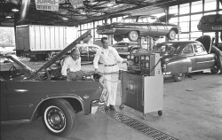 This photo captures a Chevrolet dealership service department in the 1960s.  In the foreground is a 1965 Impala, and on the closest service bay is a 1949 Chevrolet.